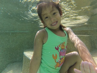 Child holding her breathe and opening her eyes under water during swimming lessons.