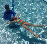 Child practicing back floats during swimming lessons.