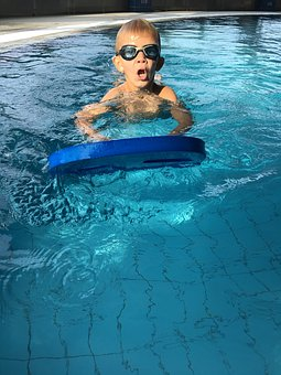 Boy practicing his breaststroke kick with a kick board.