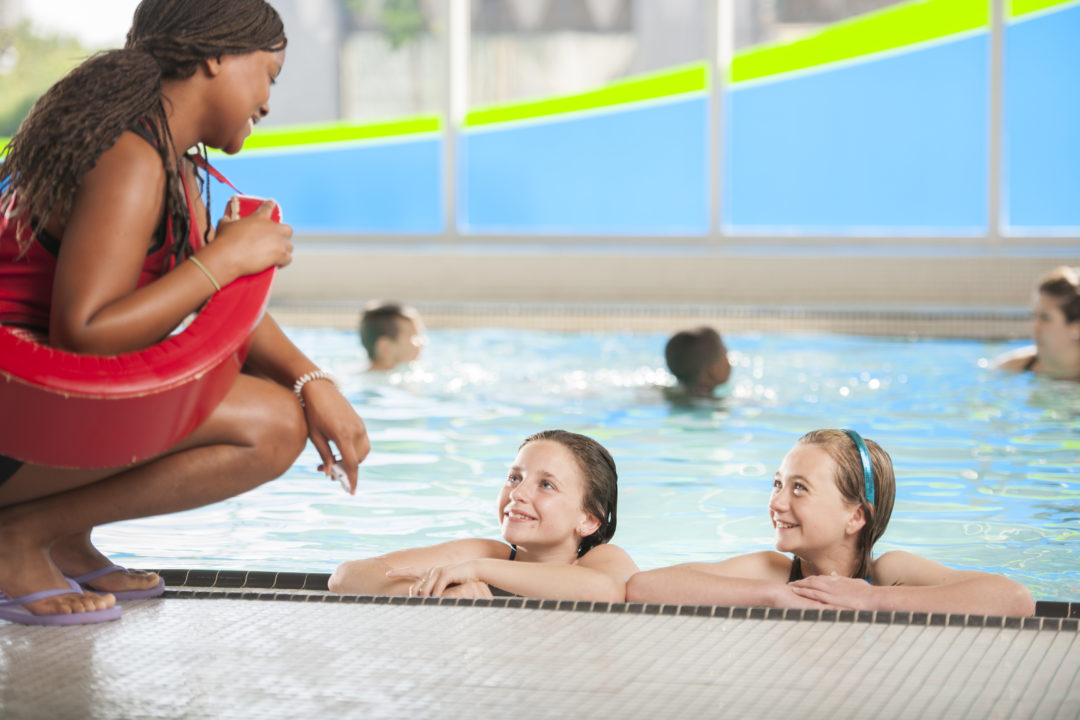 Lifeguard discussing pool rules with two swimmers